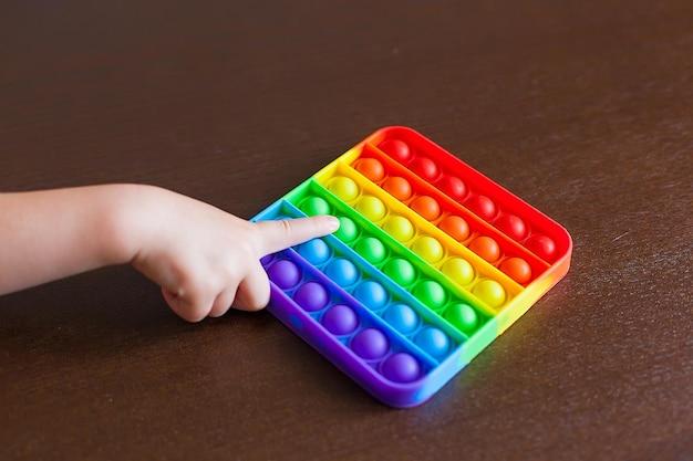 Dziecko bawiące się tęczą macha nią, naciskając bąbelki palcami, widok z góry. obraz kliknięć po bokach nowej zabawki antystresowej dla dzieci i dorosłych. otwórz