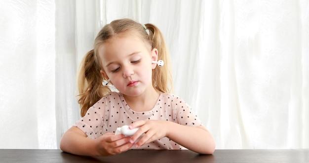 Dziecko bawiące się tws wkładkami dousznymi białym tłem
