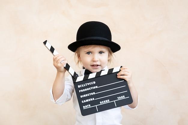 Dziecko bawiące się w domu. dziecko trzyma deskę grzechotki. koncepcja kina retro