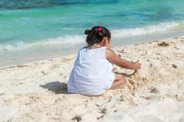 Dziecko bawiące się w piasku w pobliżu morza. mała dziewczynka siedzi na plaży. sylwetka dziewczynki z morzem. budowa zamku z piasku