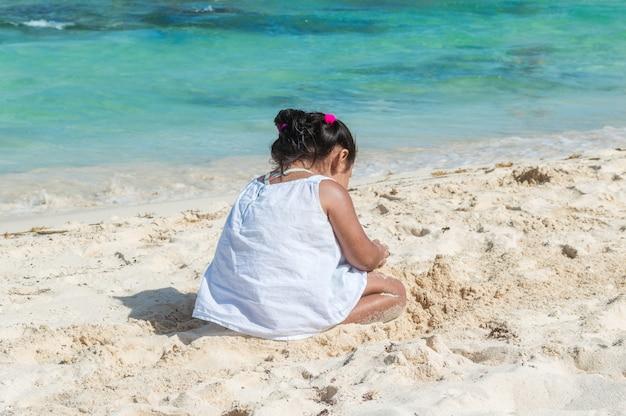 Dziecko bawiące się w piasku w pobliżu morza. mała dziewczynka siedzi na plaży. sylwetka dziewczynki z morzem w tle. budowa zamku z piasku