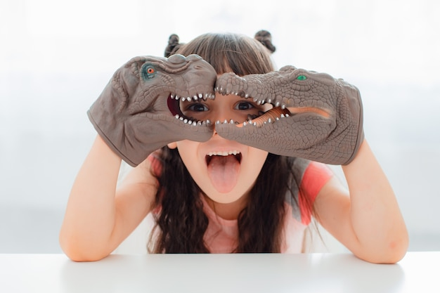 Dziecko bawiące się z gumowymi ręcznie odzianymi zabawkami dinozaurów. edukacyjne rozwijające gry fabularne dla dzieci. dzieci dziewczynka emocjonalnie bawią się zabawkami z dinozaurami. ewolucja gra paleontologiczna dla małego dziecka.