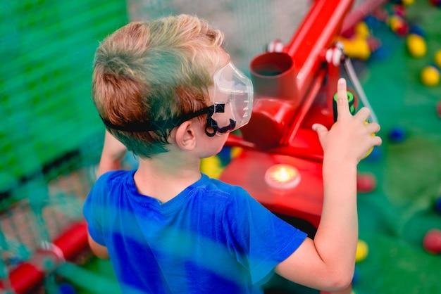 Dziecko bawić się na lato jarmarku z działem barwione piłki sprężony powietrze.