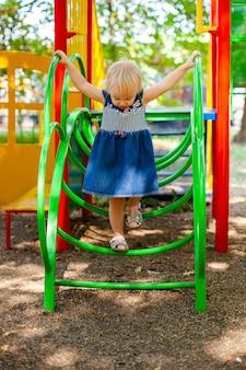 Dziecko bawić się na plenerowym boisku. mała dziewczynka gra na podwórku szkoły lub przedszkola