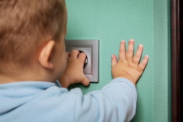 Dziecko bawić się z elektrycznym ujściem na podłoga w domu.