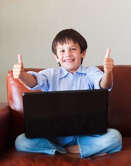 Dziecko bawić się z jego laptopem z aprobatami