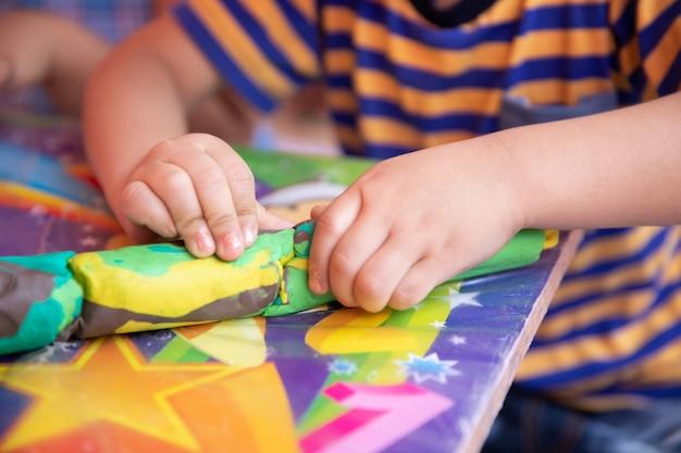Dziecko bawić się z kolorową gliną robi zwierzęciem postacie - zbliżenie na rękach