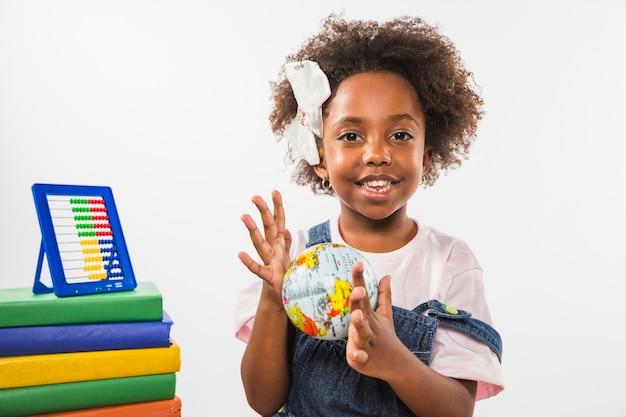 Dziecko bawić się z kulą ziemską w studiu