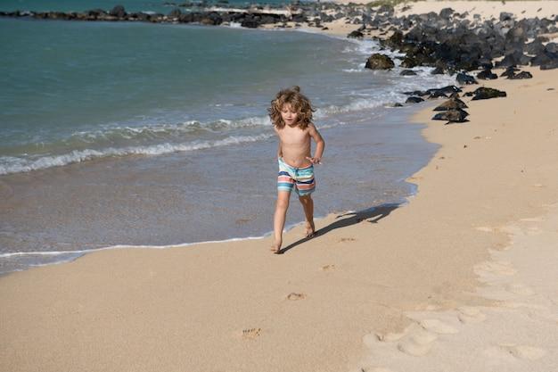 Dziecko biega na plaży. szczęśliwe dziecko biegać w morzu na letnie wakacje. podróż i przygoda na morzu lub oceanie.
