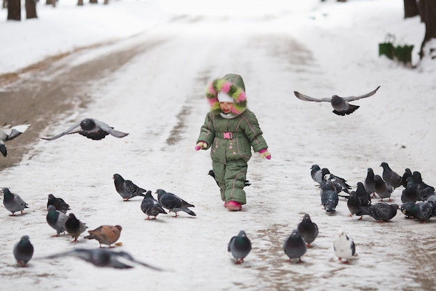 Dziecko biegnie przez stado gołębi