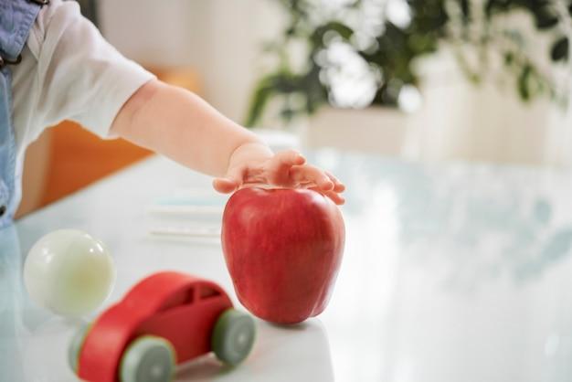 Dziecko biorąc czerwone jabłko