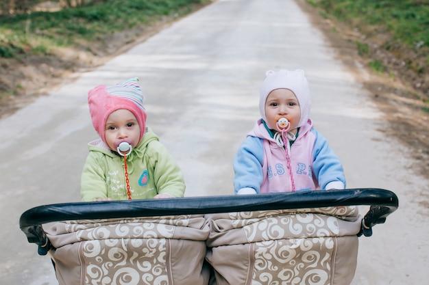 Dziecko bliźniaków w podwójnym wózku na zewnątrz