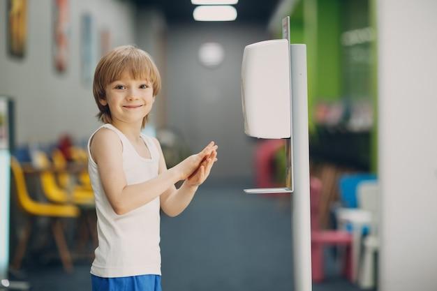 Dziecko chłopiec dziecko korzystające z automatycznego dozownika żelu alkoholowego rozpylającego na ręce urządzenie do dezynfekcji rąk antyseptyczny środek dezynfekujący nowe normalne życie po koronawirusie covid pandemia