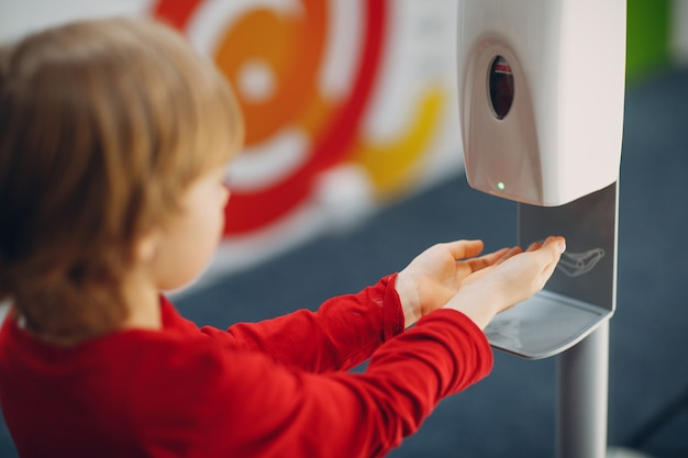 Dziecko chłopiec dziecko korzystające z automatycznego dozownika żelu alkoholowego rozpylanie na ręce maszyna do dezynfekcji antyseptyczny środek dezynfekujący nowe normalne życie po pandemii koronawirusa