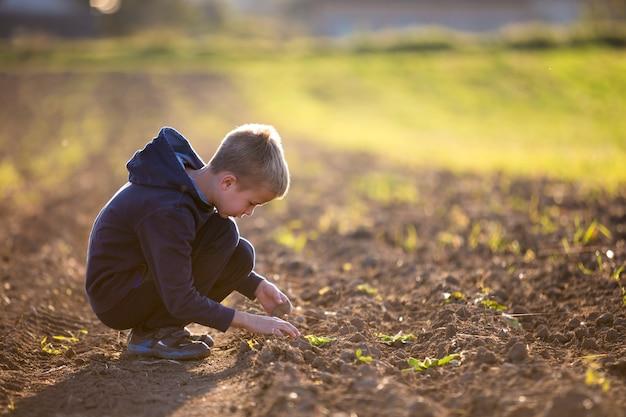 Dziecko chłopiec kuca samotnie w pustym polu