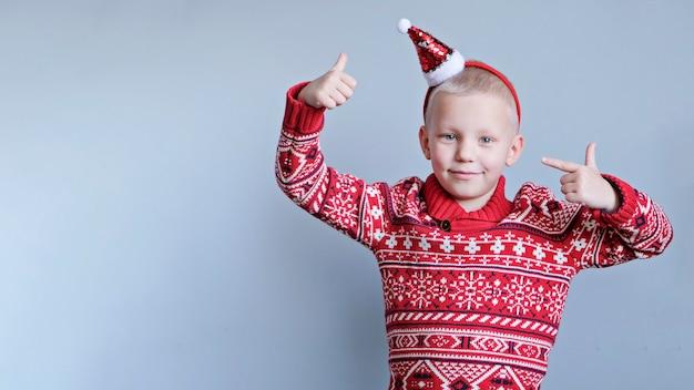 Dziecko, chłopiec w boże narodzenie czerwony kapelusz i sweter na szarym tle. koncepcja nowego roku i świąt.