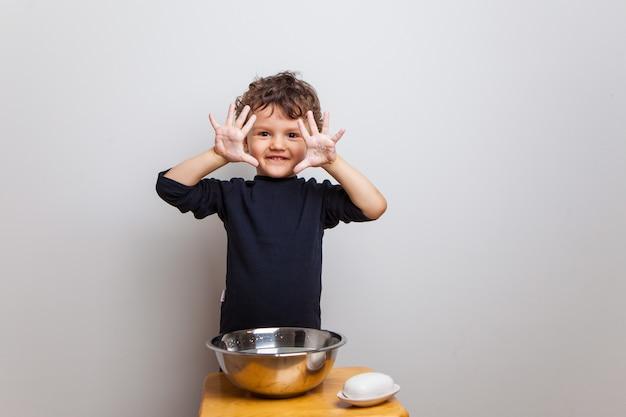 Dziecko, chłopiec w czarnej koszulce myje ręce mydłem na białej ścianie