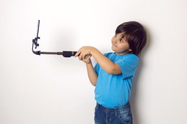 Dziecko chłopiec w niebieskiej koszulce stoi przy ścianie białej ściany z telefonem i kijem do selfie