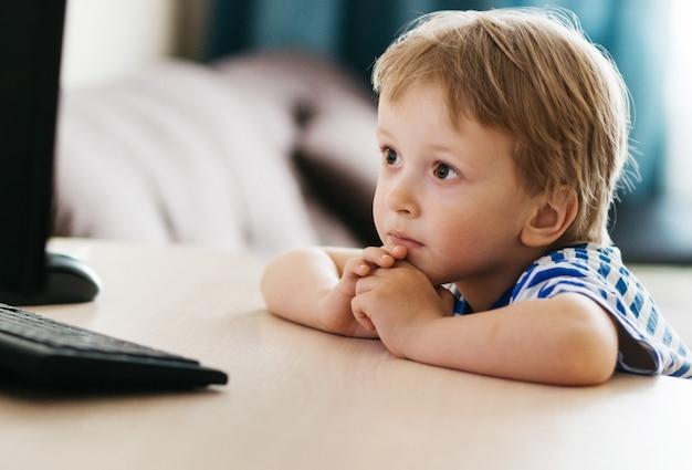 Dziecko, chłopiec w żółtej kurtce, siedzi przy stole w domu, patrząc na laptopa, uczenie się online, uczenie się na odległość w domu przez internet. technologia, szkoła, wiedza.