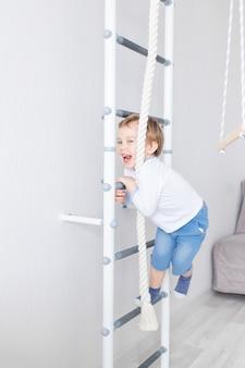 Dziecko chłopiec wspina się na szwedzkiej ścianie domu wall