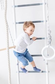 Dziecko, chłopiec, wspina się na szwedzkiej ścianie domu.