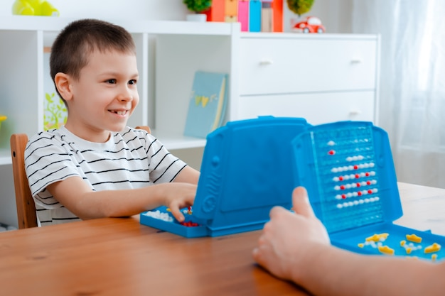 Dziecko chłopiec z tatą grające w okręty wojenne i okręty podwodne są umieszczane na boisku w pancerniku gry. zabawa