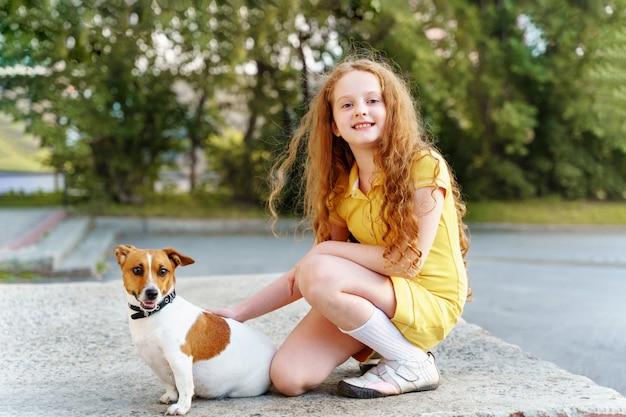 Dziecko chodzi z jej szczeniaka dźwigarką russell.