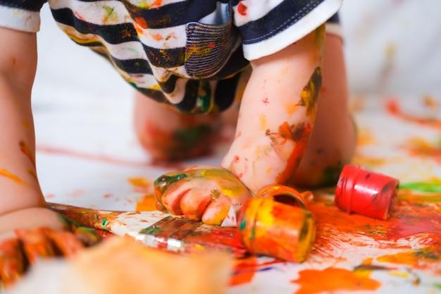 Dziecko czołga się po podłodze, bawiąc się farbami