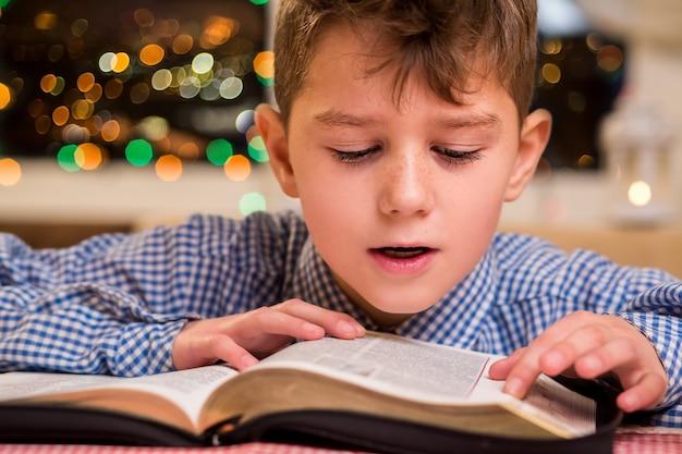 Dziecko czyta książkę na głos. chłopiec czyta książkę w nocy. utrwalanie wiedzy na temat przedmiotu. powtarza i zapamiętuje.