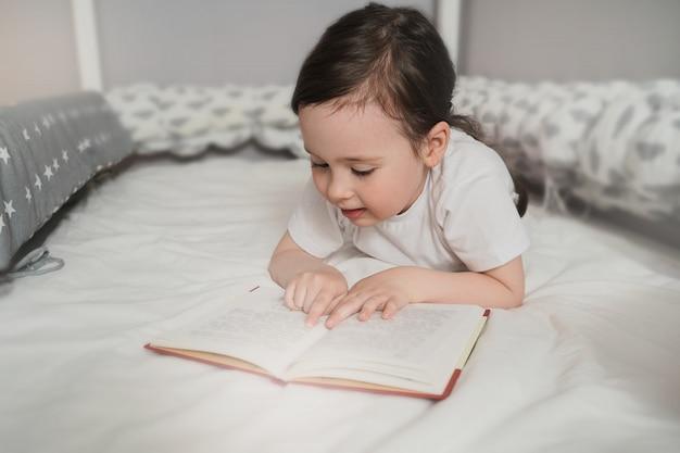 Dziecko czyta książkę przed snem w swoim łóżku. dziewczyna schowała się pod kołdrą i czyta. maluch ukrywa się w różowym kocu.