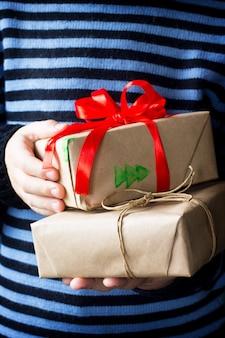 Dziecko dające boże narodzenie przedstawia pudełko z czerwoną wstążką