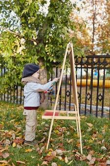 Dziecko dla dzieci w ubrania retro wiosna jesień. małe dziecko siedzi uśmiecha się w przyrodzie, szalik
