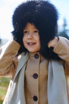 Dziecko dla dzieci w ubrania retro wiosna jesień. małe dziecko siedzi uśmiecha się w przyrodzie