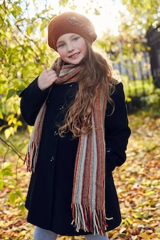 Dziecko dla dzieci w ubrania retro wiosna jesień. małe dziecko siedzi uśmiechnięte w naturze, szalik na szyi, chłodna pogoda. jasne emocje na jego twarzy. ,