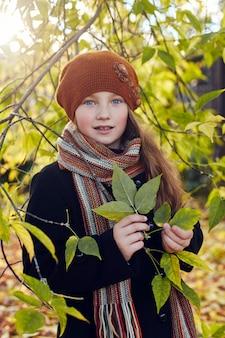 Dziecko dla dzieci w ubrania retro wiosna jesień. małe dziecko siedzi uśmiechnięte w naturze, szalik na szyi, chłodna pogoda
