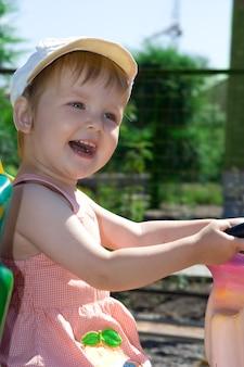 Dziecko dobrze się bawi na atrakcji w parku latem