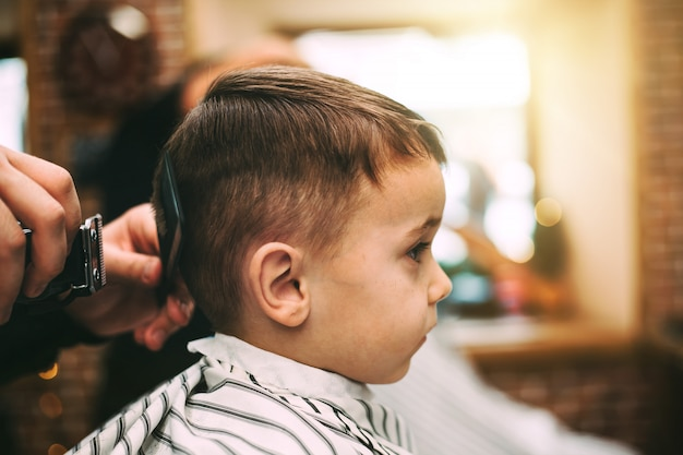 Dziecko dostaje fryzurę w sklepie fryzjerskim