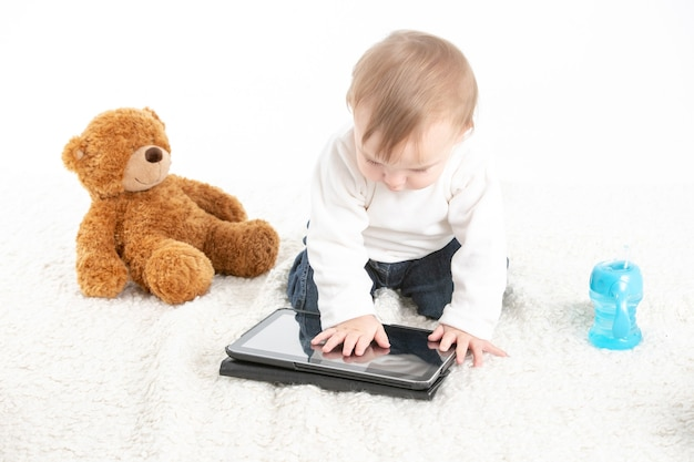 Dziecko dotykające ekranu tabletu z misiem na boku i pojemnikiem z uchwytami do picia.