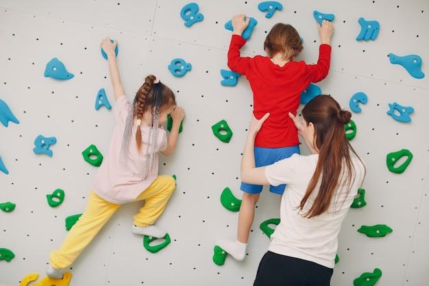 Dziecko dziecko na ściance wspinaczkowej dzieci uprawiają zdrowy tryb życia w przedszkolu lub centrum sportowym w szkole