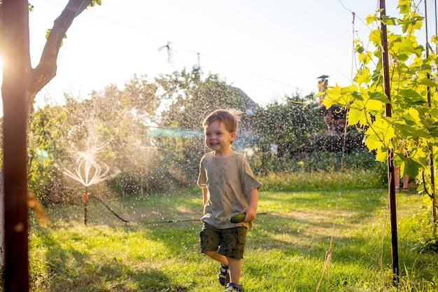 Dziecko dziecko podczas zabawy z laską wodną w ogrodzie. koncept: wolność, szczęście, czas wolny.
