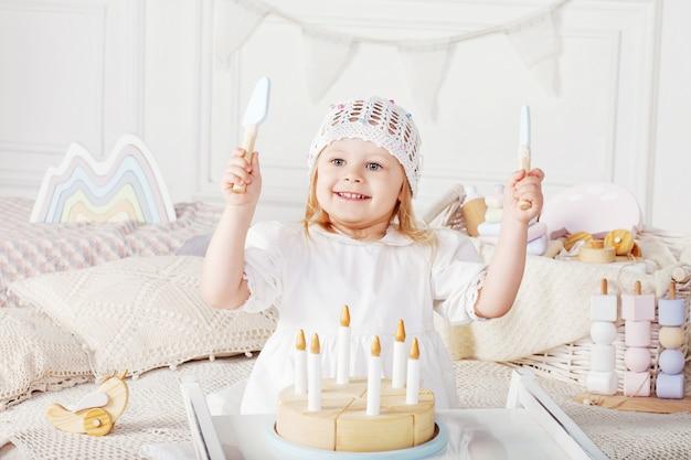 Dziecko dziewczyna bawić się z drewnianym zabawka tortem.