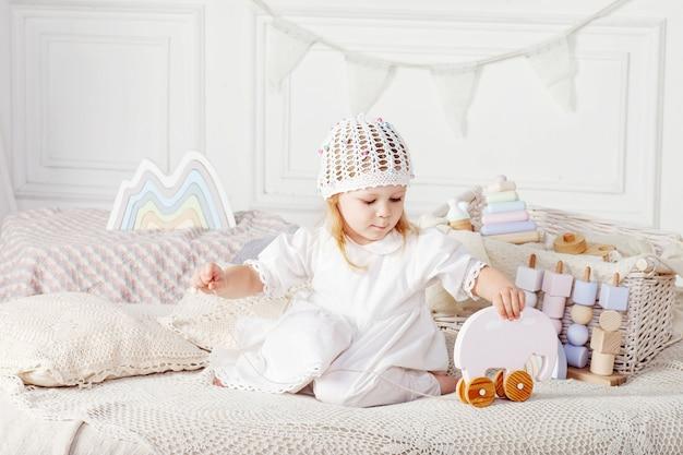 Dziecko dziewczyna bawić się z drewnianymi zabawkami.