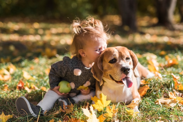 Dziecko dziewczyna całuje jej psiego obsiadanie w trawie przy lasem