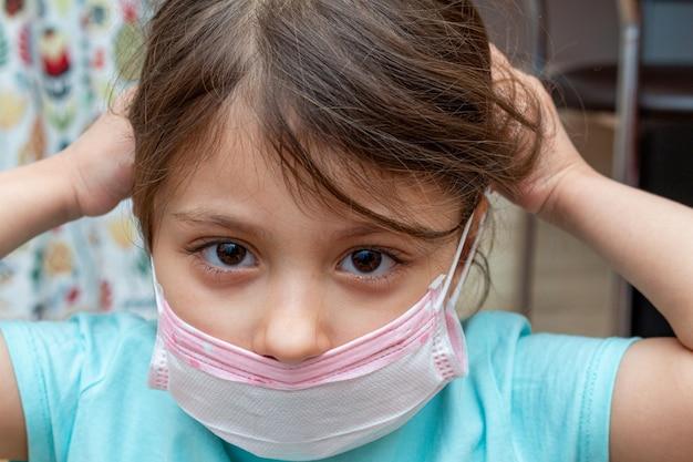 Dziecko dziewczyna jest ubranym medyczną ochronną maskę w domu podczas kwarantanny odosobnienia