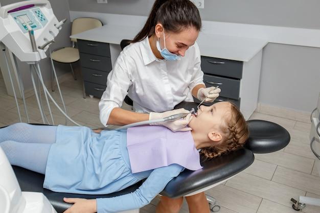 Dziecko dziewczyna ma fachowego stomatologicznego cleaning w dentysty biurze