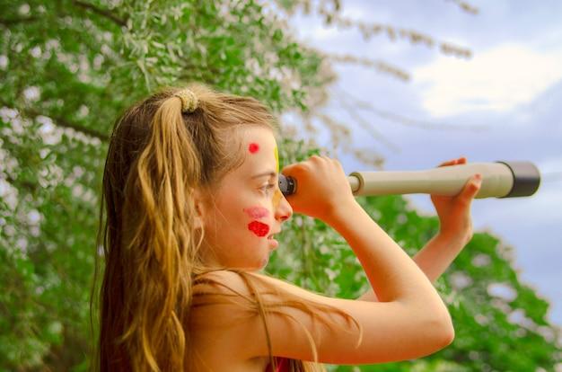 Dziecko dziewczyna patrzeje przez wziernego szkła w obozie letnim