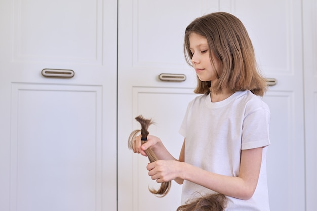 Dziecko dziewczyna pokazuje przycięte włosy, fryzjer w domu, miejsce.