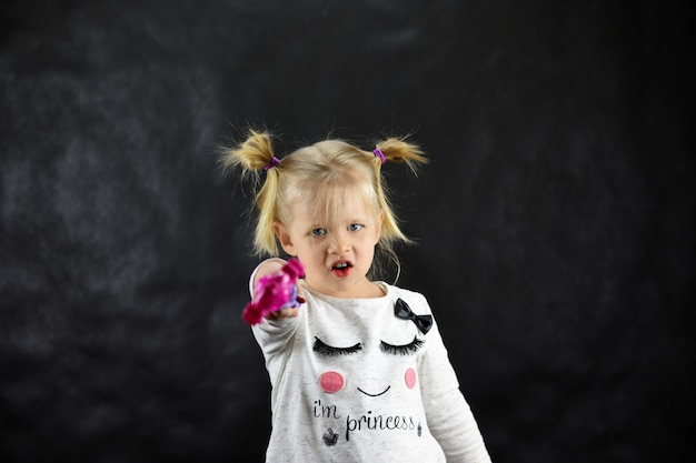 Dziecko dziewczyna wyczarowuje magiczną różdżkę na czarnym tle