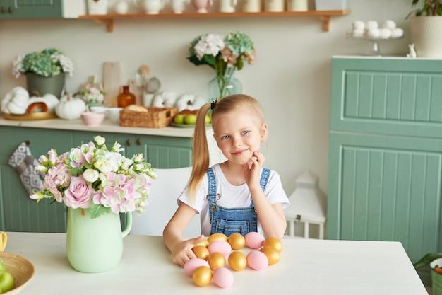 Dziecko dziewczyna z easter jajkami w kuchni. wesołych świąt wielkanocnych koncepcji. szczęśliwa rodzina przygotowuje się do wielkanocy.
