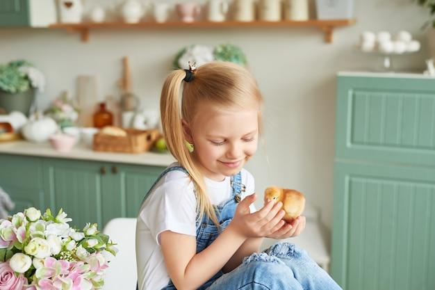 Dziecko dziewczyna z easter kurczakami w kuchni i jajkami. wesołych świąt wielkanocnych koncepcji. szczęśliwa rodzina przygotowuje się do wielkanocy.